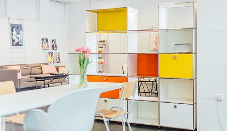 White, yellow and orange USM Haller room divider in a creative office