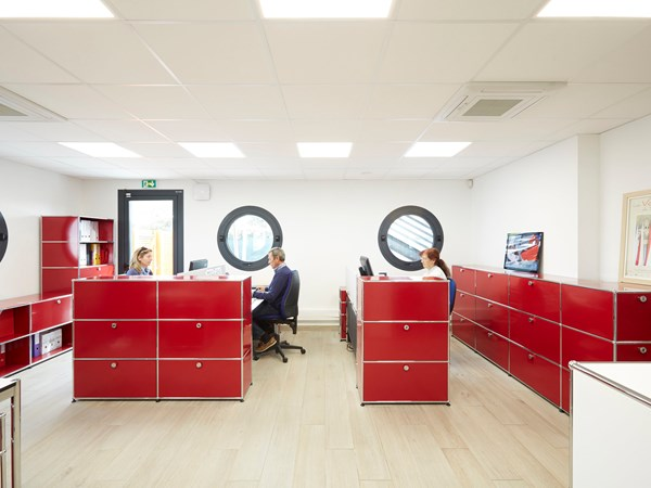 Red USM Haller room dividers creating space in open plan office