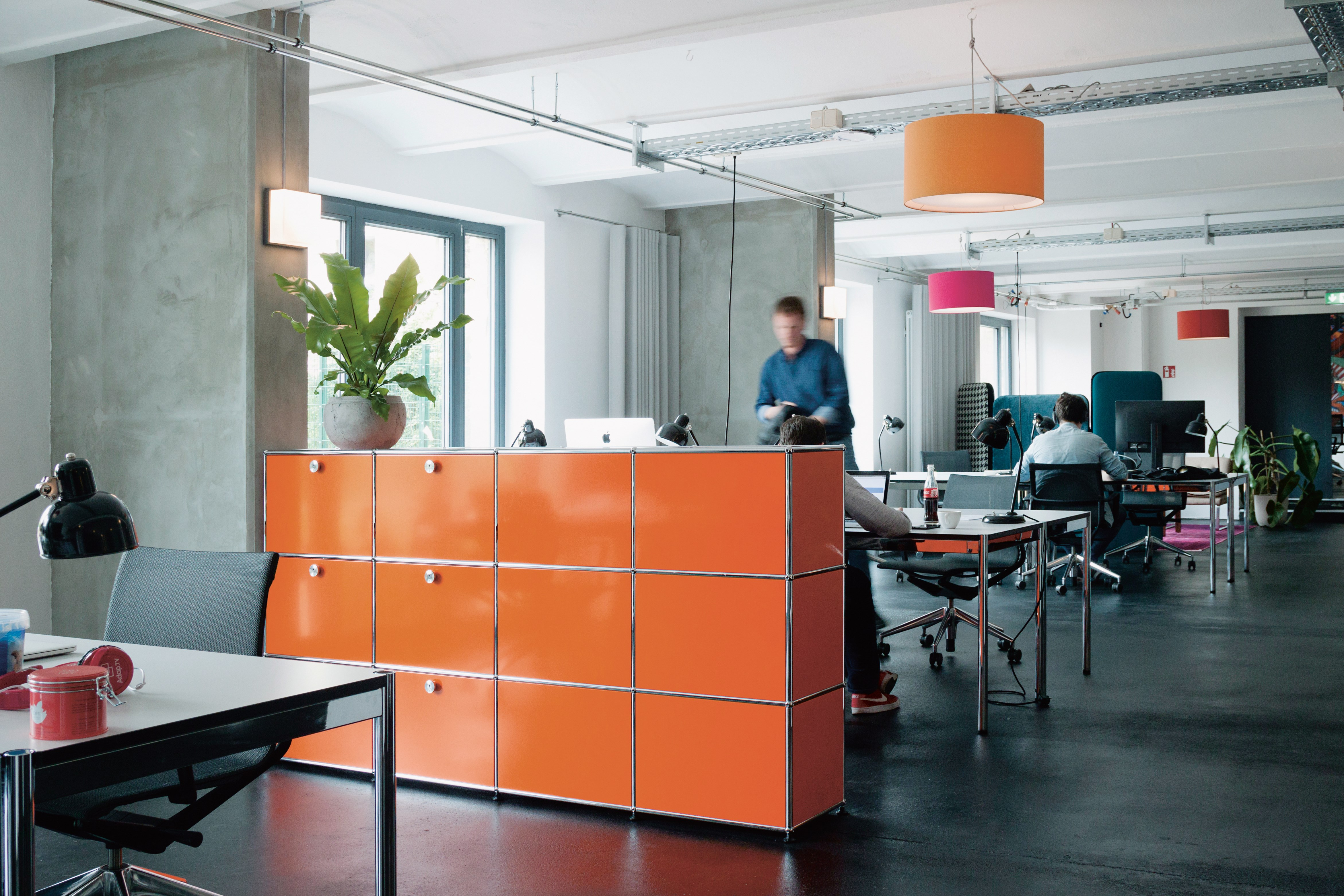 orange and chrome USM haller office partition with storage cabinets in a contemporary office
