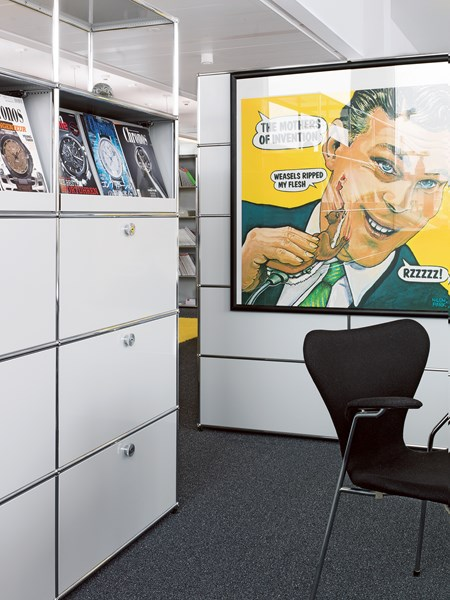 white and chrome modular storage with magazine display shelves in an office break area