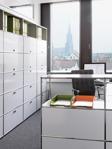 white and chrome USM haller fillling cabinets in a office cubical