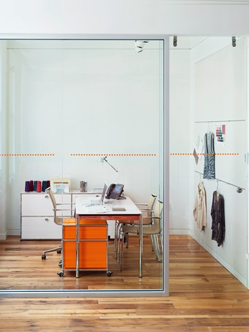 private office with white USM Haller table and orange pedestal on castors