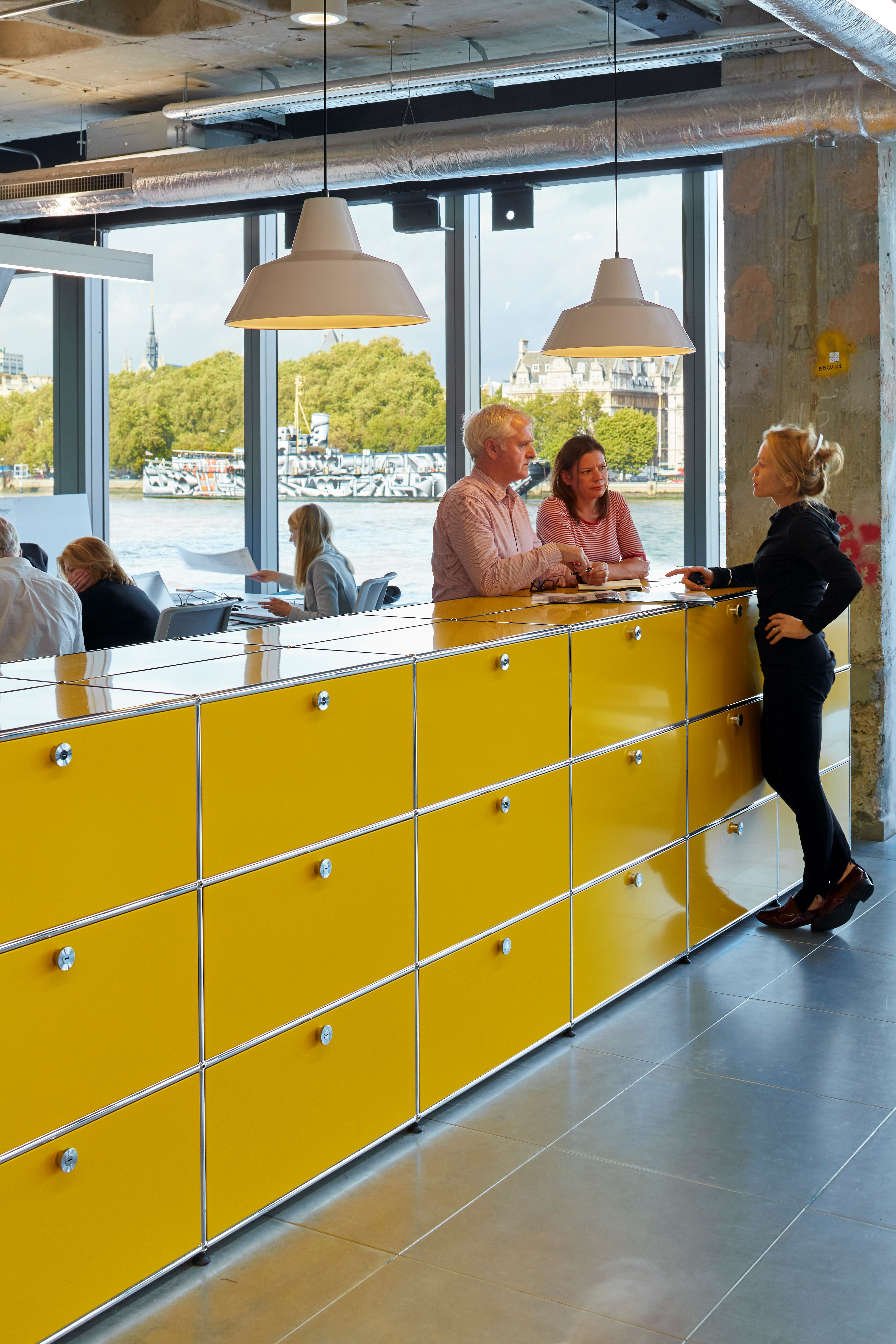 golden yellow USM haller office dividers with storage cabinets in an industrial style office