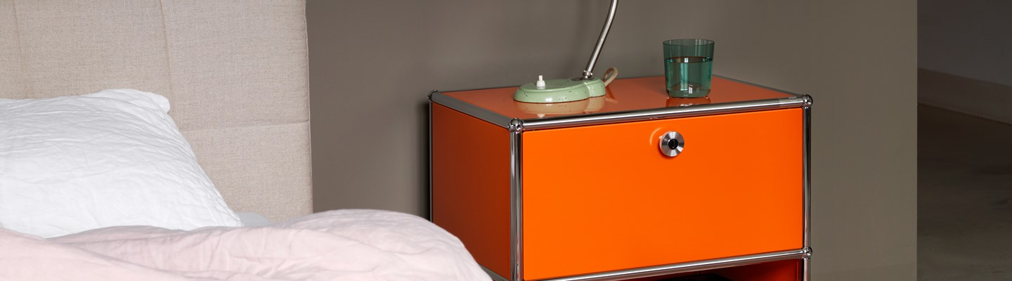 orange USM Haller bedside table in a modern bedroom with one door