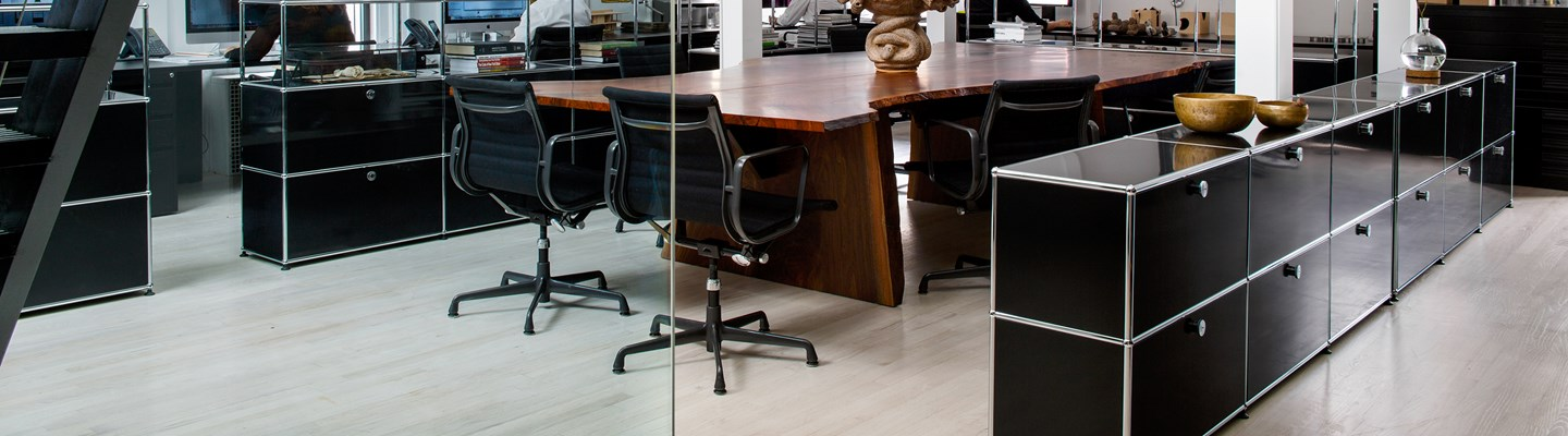 black USM Haller storage units for office desks working as room dividers