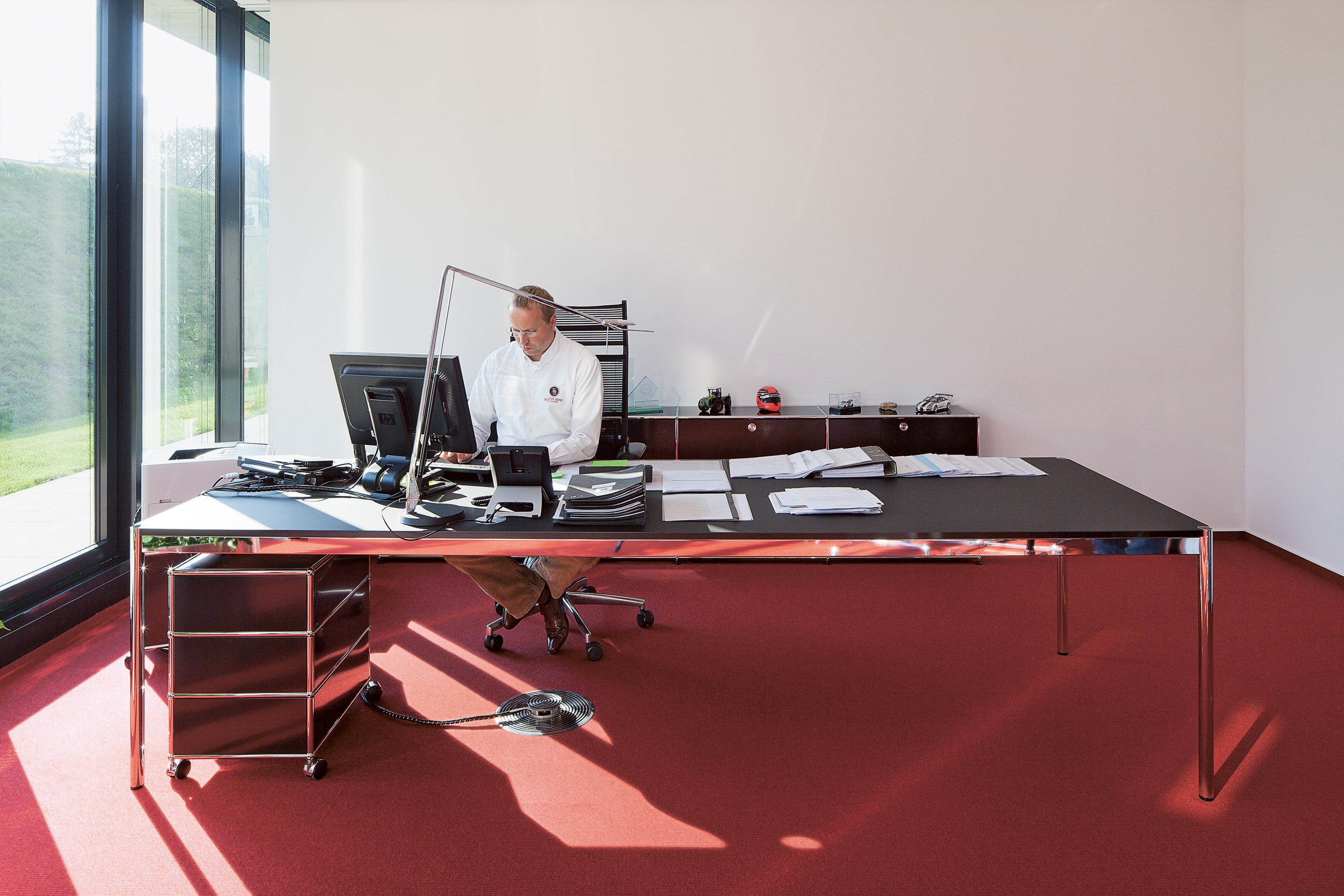 black USM Haller desk and pedestal in red and white executive office