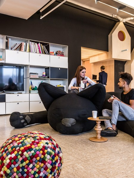 informal meeting area with beanbags and USM Haller white media unit