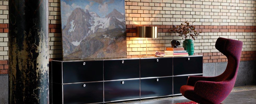 black USM Haller sideboard with industrial brickwork and original flooring