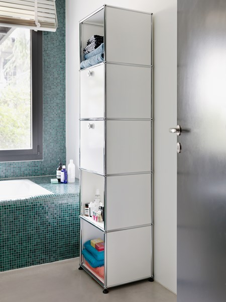 pure white metal USM haller shelving and draws in a tiled bathroom