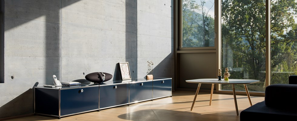blue metal USM haller sideboard storage with draws in a brightly-lit livingroom