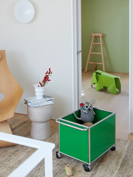 playful green USM Haller children's toy storage trolley in modern home