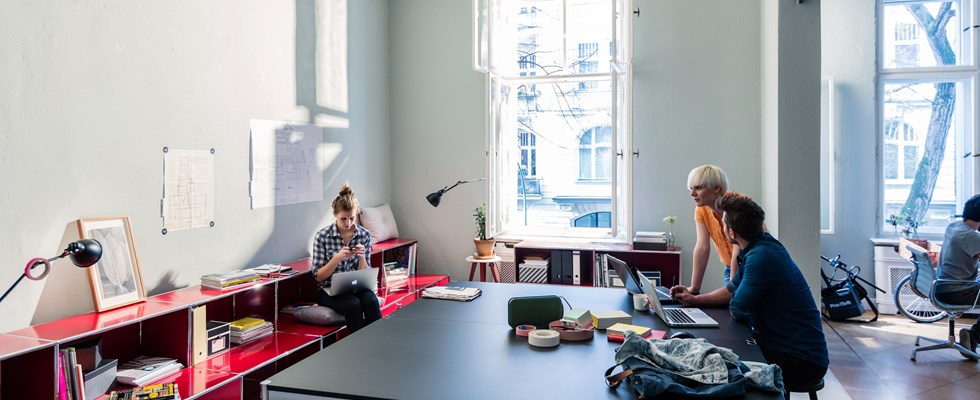 office breakout area with black USM Haller table and red storage with seating