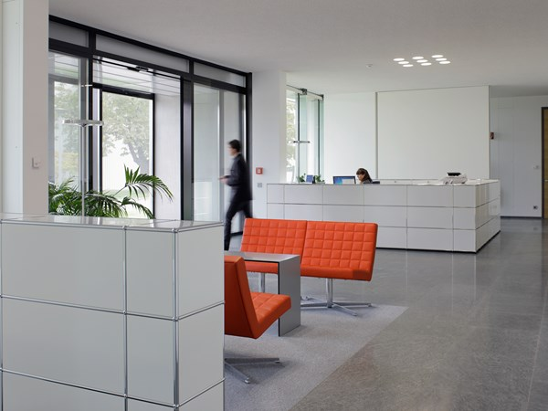 white USM Haller furniture in modern reception area with orange chairs