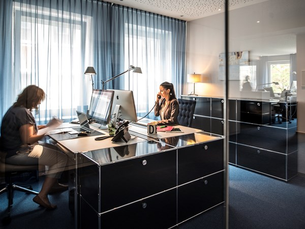 black USM Haller sideboards and workstations in a modern open plan private office