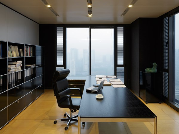 stylish executive office with black USM Haller table and storage pieces