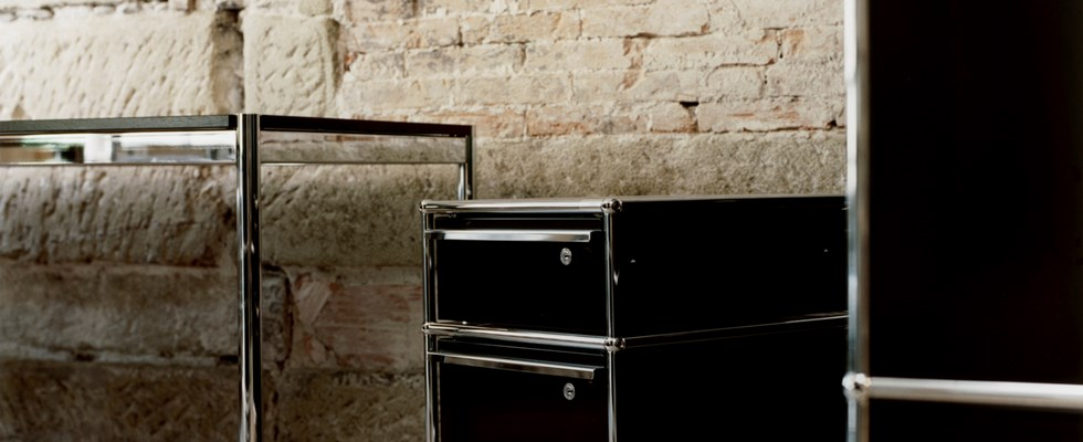 chrome and black USM haller pedestal with draw storage in a barebrick bathroom