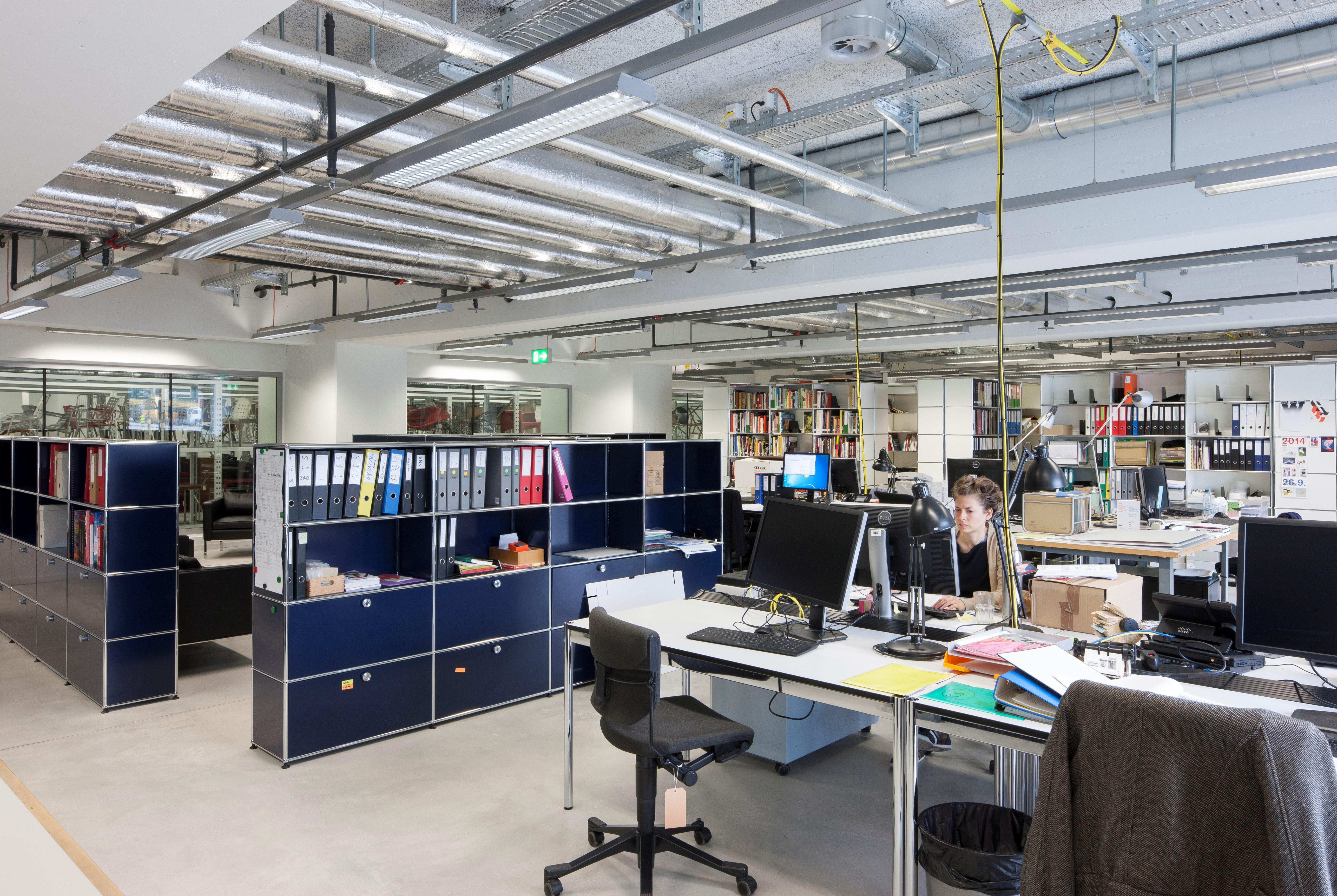 open plan industrial office with USM Haller filing cabinets and workstations