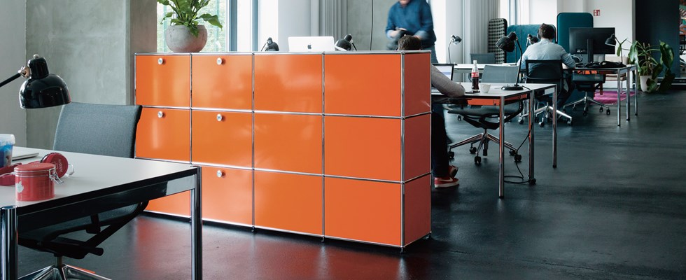 casiers de bureau personnels USM Haller orange et chrome dans un bureau contemporain