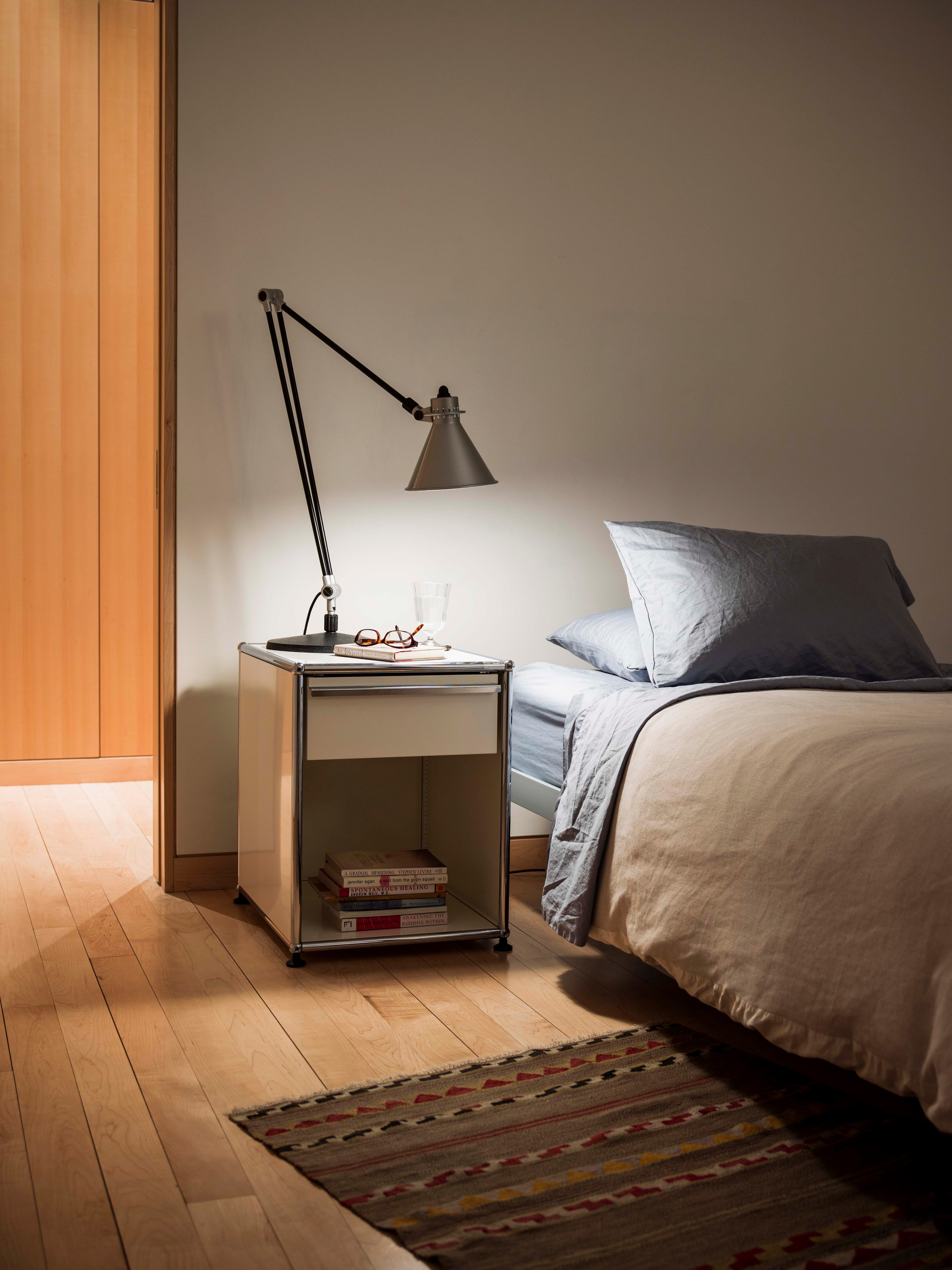 white USM Haller bedside table with lamp and books