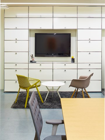 pure white USM haller tv unit with storage cabinets in a an office breakout area