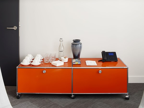 small orange USM Haller sideboard on wheels with closed storage in modern meeting room