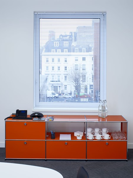 orange USM Haller sideboard with open and closed storage hiding hifi system in modern meeting room