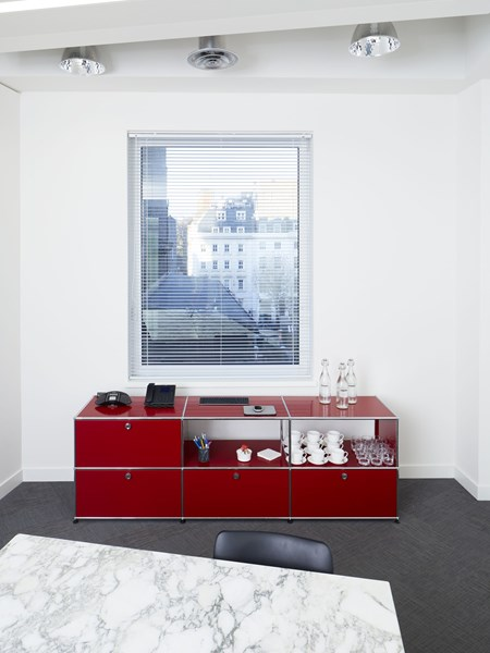 red USM Haller sideboard with open and closed storage in modern meeting room