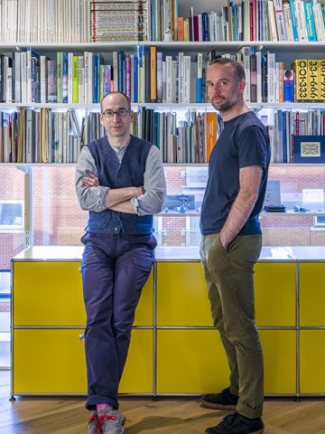 Edward Goodwin and Richard Hartshorn in their modern, open plan office with yellow USM Haller