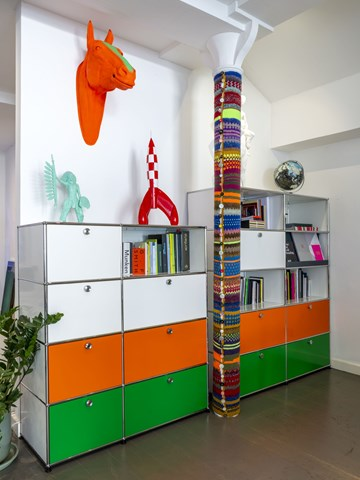 open plan creative office with orange USM Haller bookcases