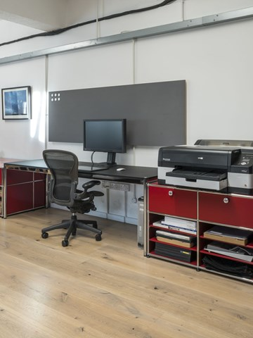 open plan photographic studio with red USM Haller storage and lino USM Haller desk
